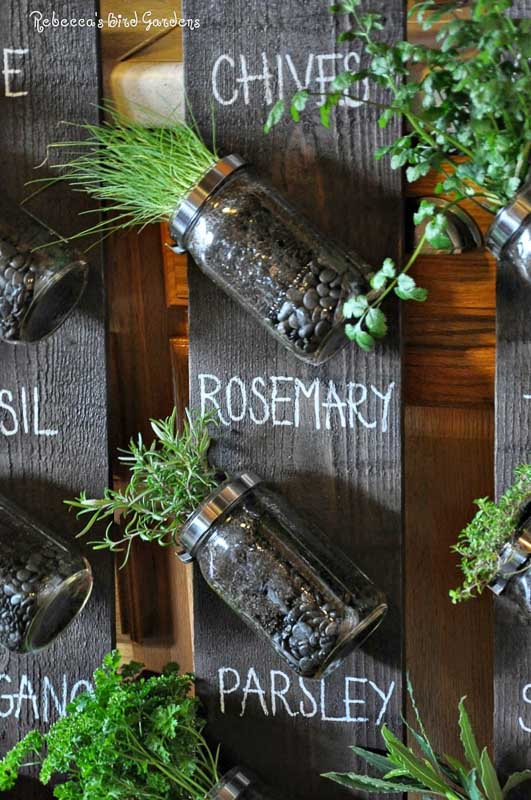 Mason jars attached to old bard wood pickets. Herbs labeled with chalk on the fence post.