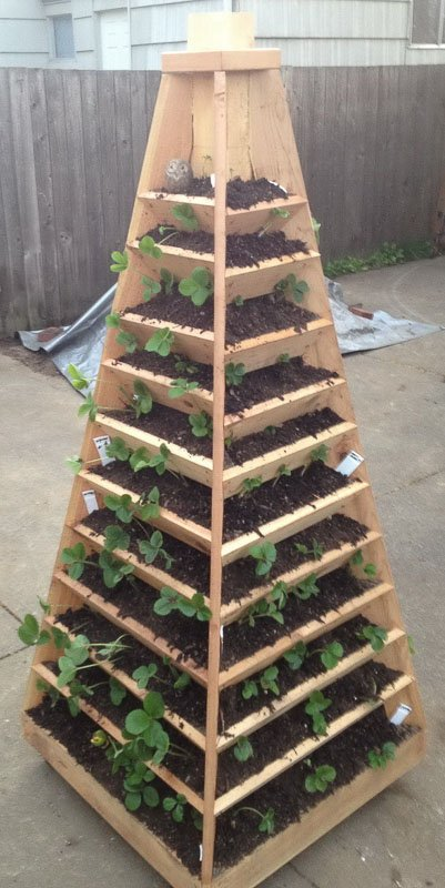A DIY pyramid-shaped free-standing, rolling vertical garden planter with multiple tiers.
