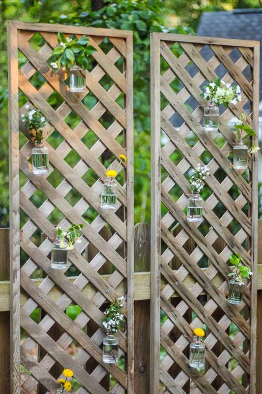 Sections of framed lattice create a DIY privacy screen from which flower vases are hung