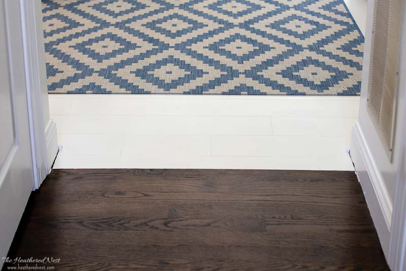 how to paint wood floors | close-up of finished white painted wood floors and the transition between the dark oak hardwoods in the rest of our house next to the painted kitchen floors