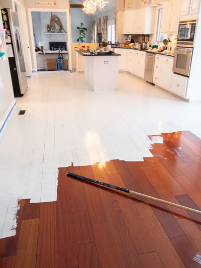 how to paint wood floors | in process of priming floors before paint - we did NOT sand!