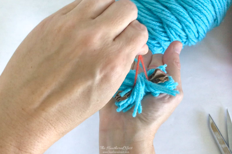 Grab the ends of the piece of yarn sandwiched between the cardboard discs in order to knot the pom pom and secure.