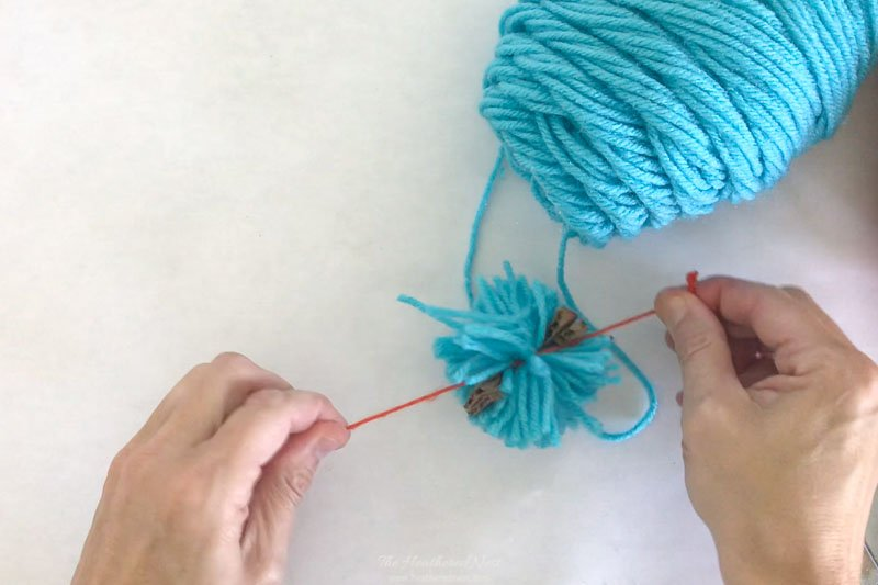 Securing DIY yarn pom pom with a tight knot.