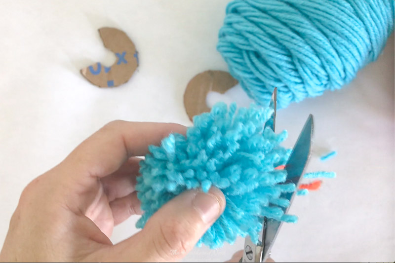 Trim yarn to uniform length around whole DIY pom pom