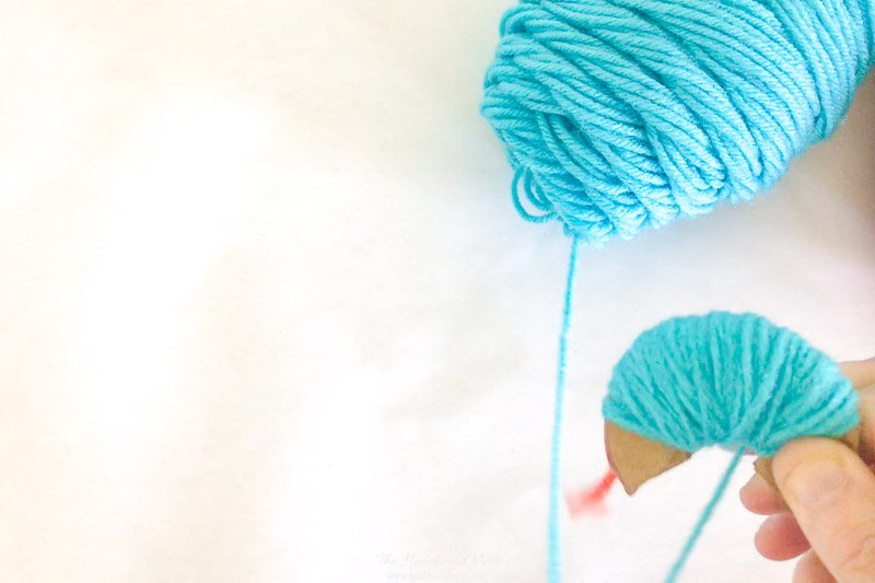Warpping Yarn Around Cardboard To Create a DIY Pom Pom