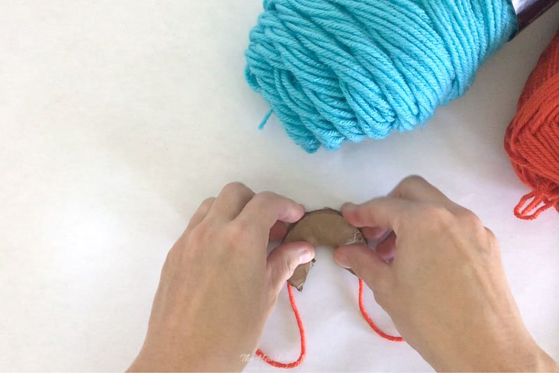Showing a section of yarn sandwiched between two c-shaped cardboard discs for this DIY pom pom making technique