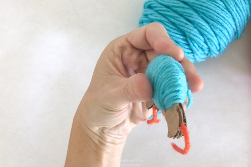 Showing the cardboard pom pom maker thickly layered with yarn prior to cutting.