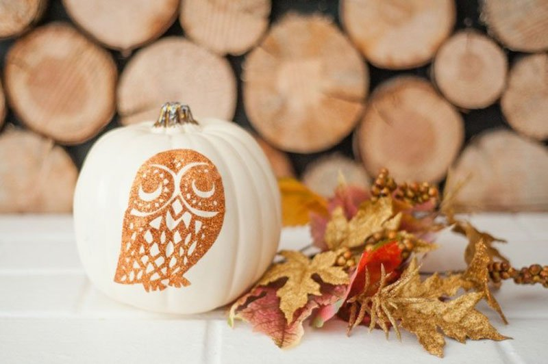 white pumpkin embellished with a glittery orange owl
