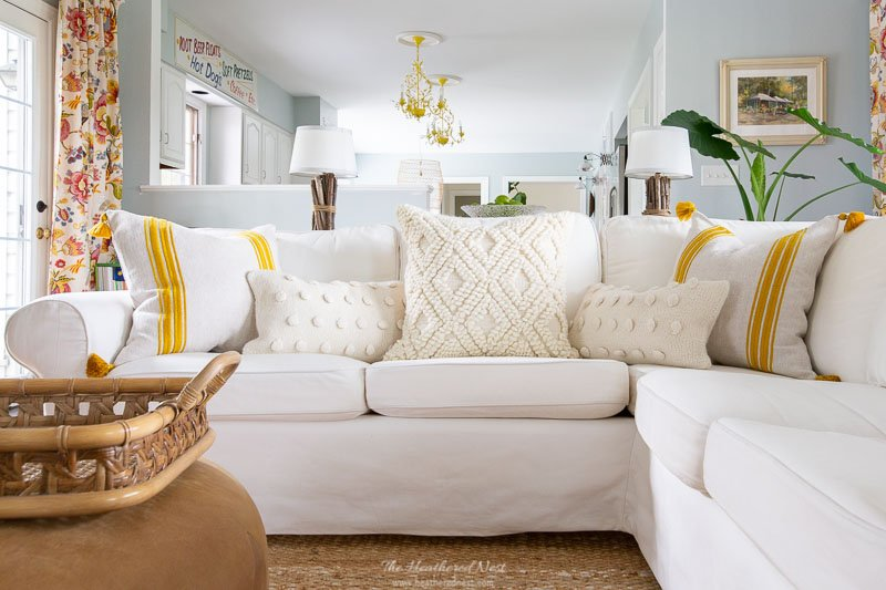 IKEA Ektorp white sectional sofa with white and yellow striped cushions