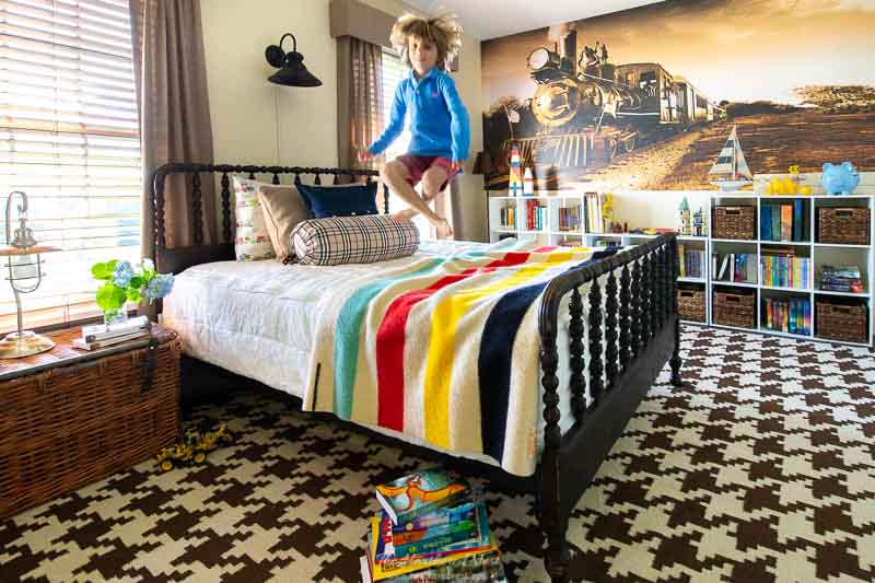 boys room with train wall mural, houndstooth rug and vintage hudson bay point blanket, jenny lind bed and boy jumping on bed