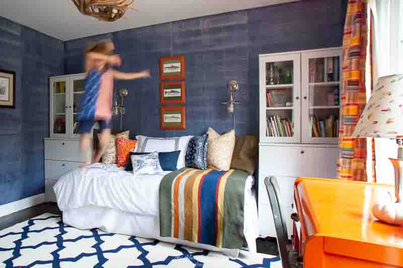 boy dabbing and jumping off bed in room with denim painted walls, geometric blue and white trellis rug, orange desk, faux antler chandelier, madras curtains and Pendleton WM Badlands blanket