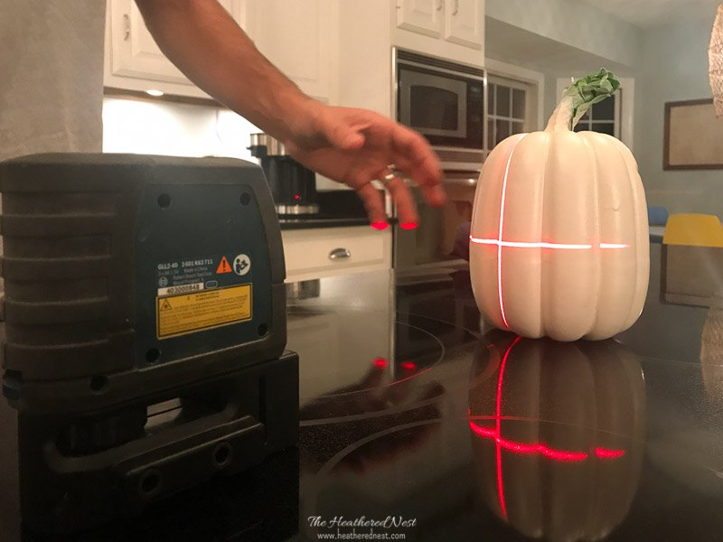 Using a laser level to draw stripes to be painted on hudson bay blanket inspired pumpkins for fall