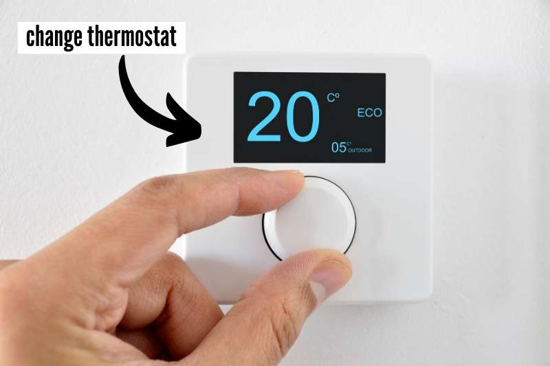 19 Things To Do At Home Before You Travel Checklist - image of thermostat being adjusted