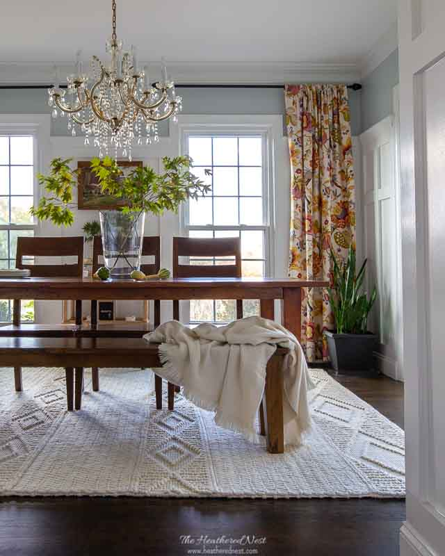 dining room with textured cream wool rug, acacia table with bench and chairs, floral curtains and gold chandelier