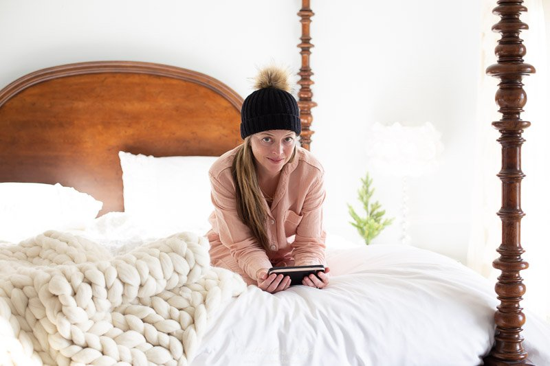 9 tips for winter hygge decor | linen pjs in bed with fuzzy pom pom hat and chunky looped henley wool throw