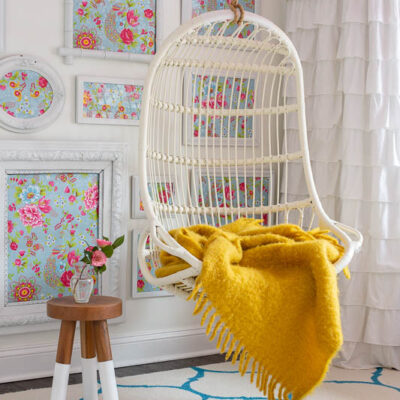 Hanging rattan indoor chair in girls bedroom