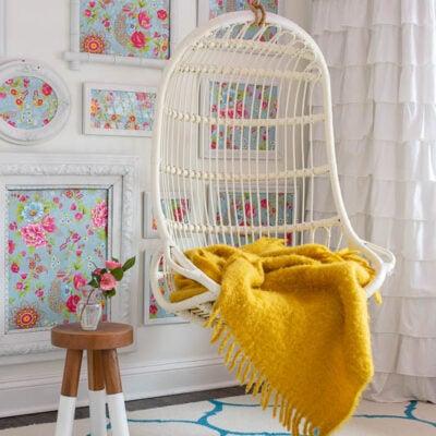 Hanging rattan indoor chair in girls bedroom