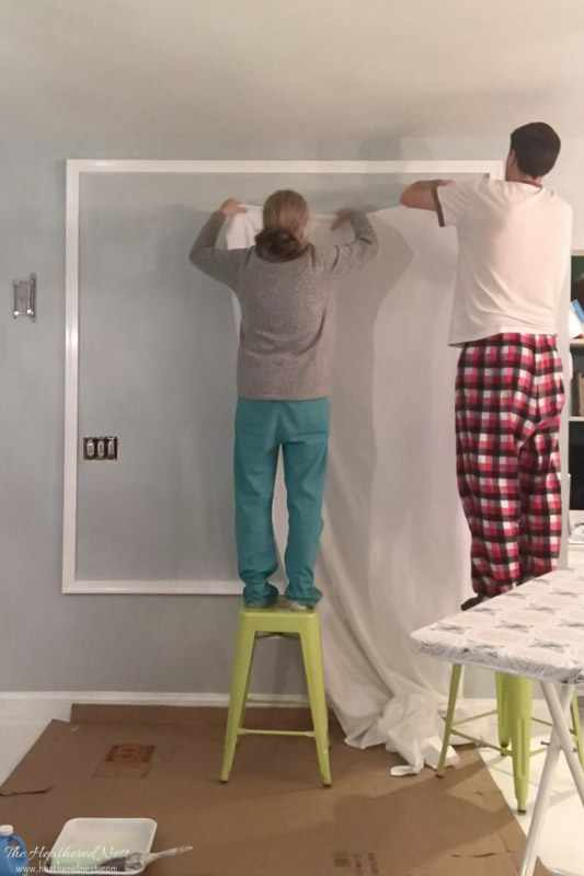 DIY Starched Fabric Wall Treatment - Start applying fabric in top corner of your wall