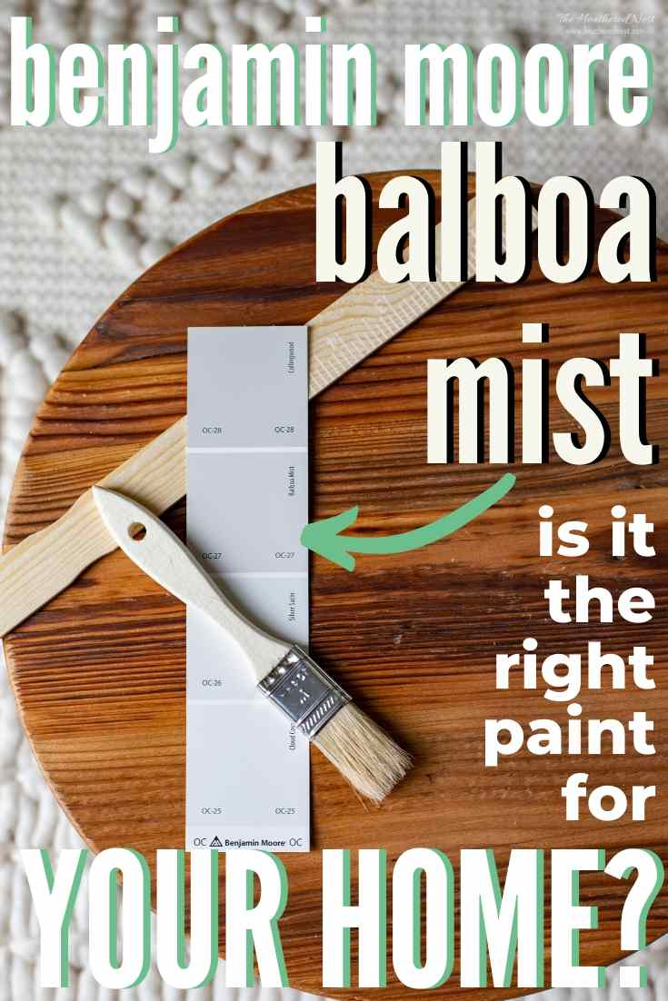 Benjamin Moore Balboa Mist next to a paintbrush on a wooden round
