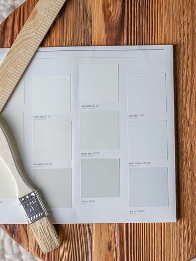 Wooden round with a paper filled with Benjamin Moore white paint chip samples.