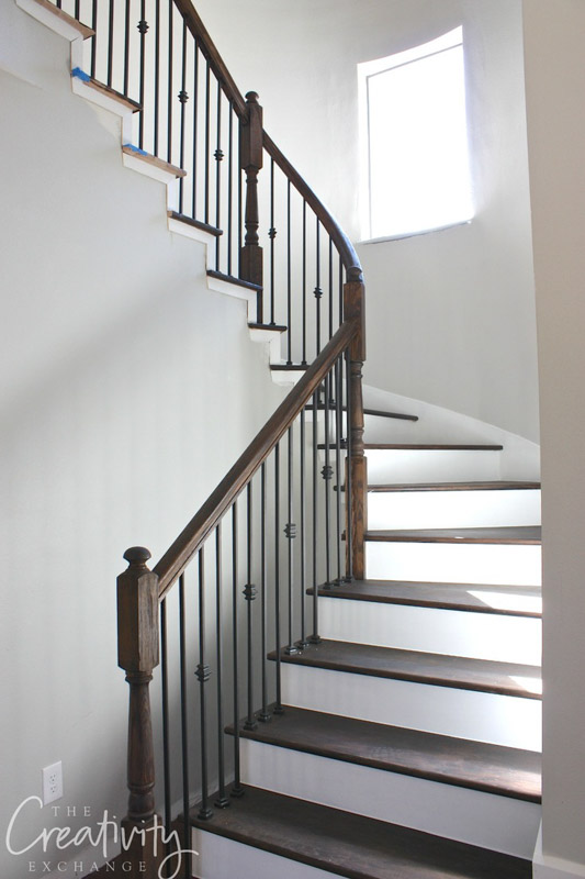 Stairwell with white risers and wooden stairs. The wall is painted Sherwin Williams Repose Gray.