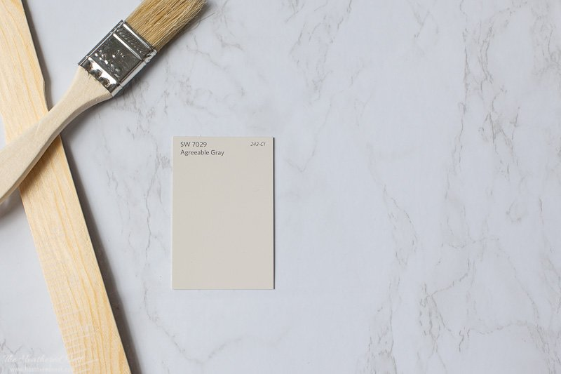Sherwin Williams Agreeable Gray paint chip on a marble background with paintbrush and paint stirrer
