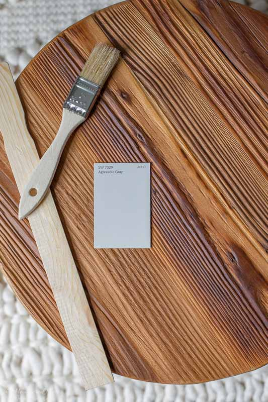 Sherwin Williams Agreeable Gray paint chip on wood background with paintbrush and paint stirrer