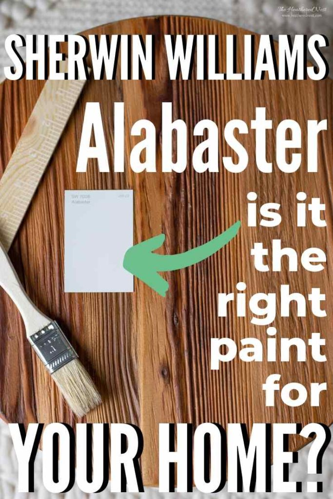 Sherwin Williams Alabaster paint chip on a wood floor with a paint brush next to it.