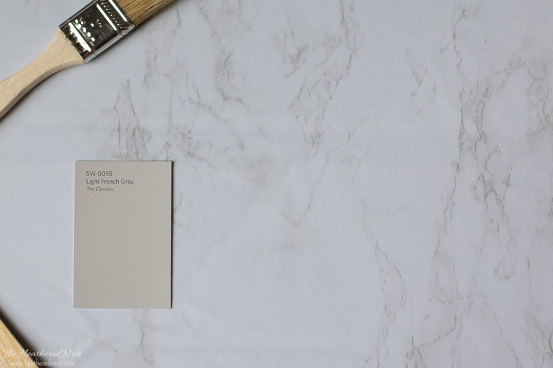 Sherwin Williams Light French Gray paint swatch on a marble background
