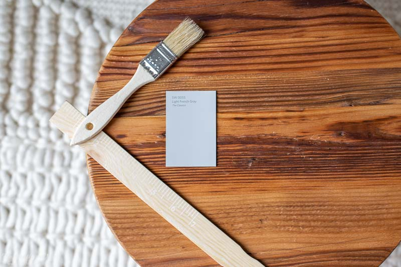 swatch of sherwin williams light french gray on a wooden round with a paintbrush and stir stick