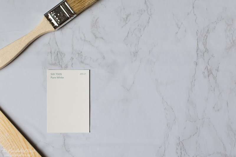 Sherwin Williams Pure White paint swatch with a paint brush