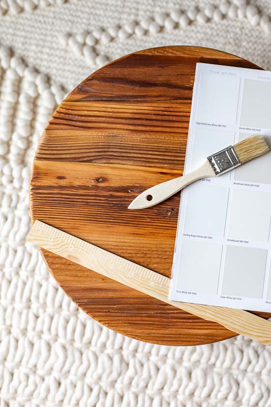 Warm white paint swatches including Sherwin Williams pure white on a wooden round.