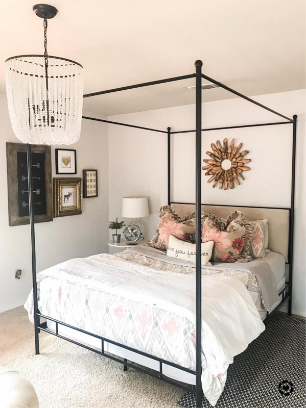 Bedroom painted Sherwin Williams Snowbound with a black iron four post bed and white beaded chandelier.