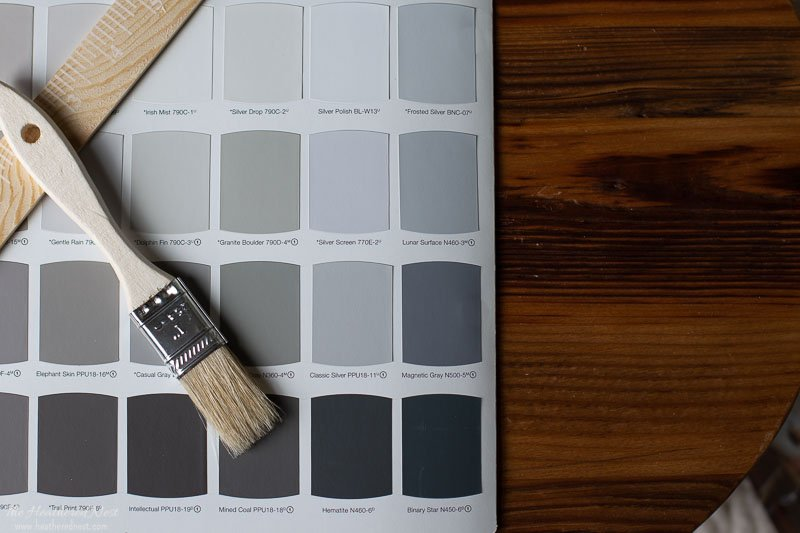 Behr Silver Drop on paint swatch card with paint brush lying on top