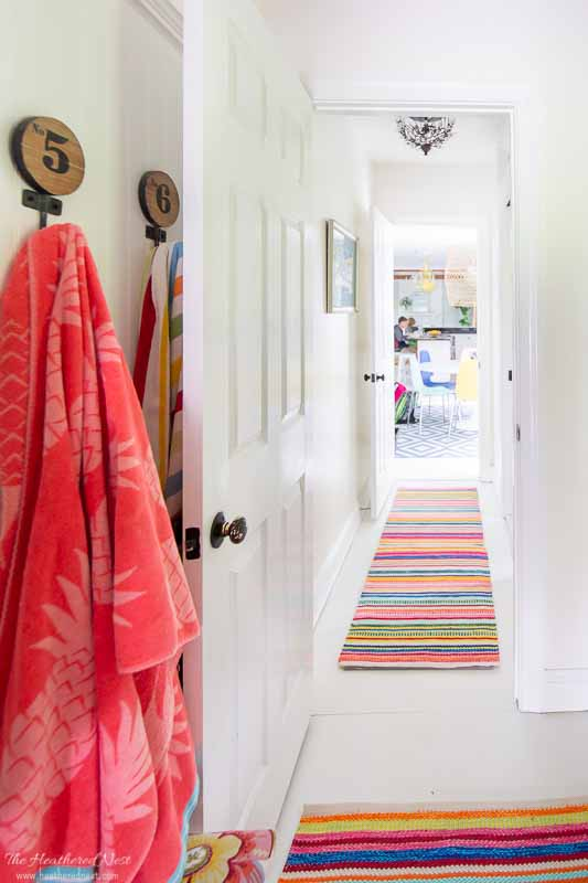 Benjamin Moore Simply White in a hallway with colorful striped rugs