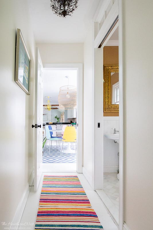 Benjamin Moore Simply White in a hallway with powder room on right and colorful striped rug in hallway