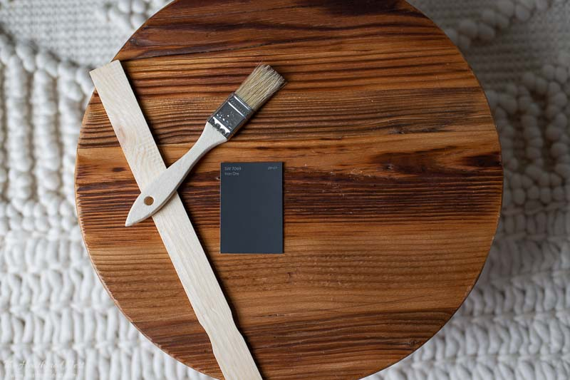 Iron ore paint swatch on a wooden round iwth a paint stick and a paint brush.