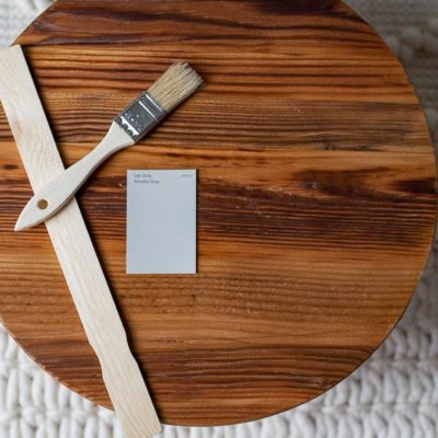 Sherwin Williams Mindful Gray swatch on wood platter with wood paint stirrer and paintbrush