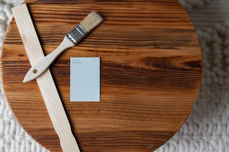 Rainwashed paint chip on a wooden round with paint brush and stir stick