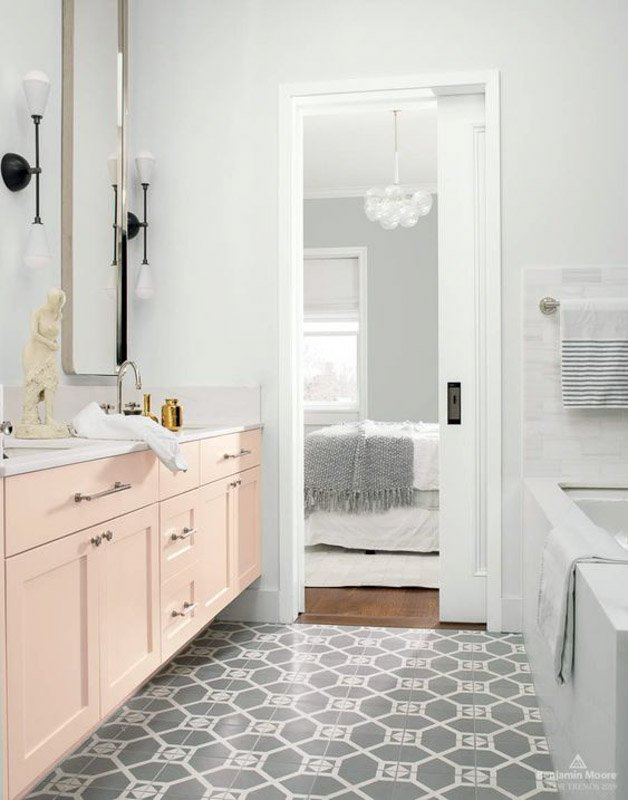 bathroom with light gray walls, white trim, peach vanity, and gray patterned floor