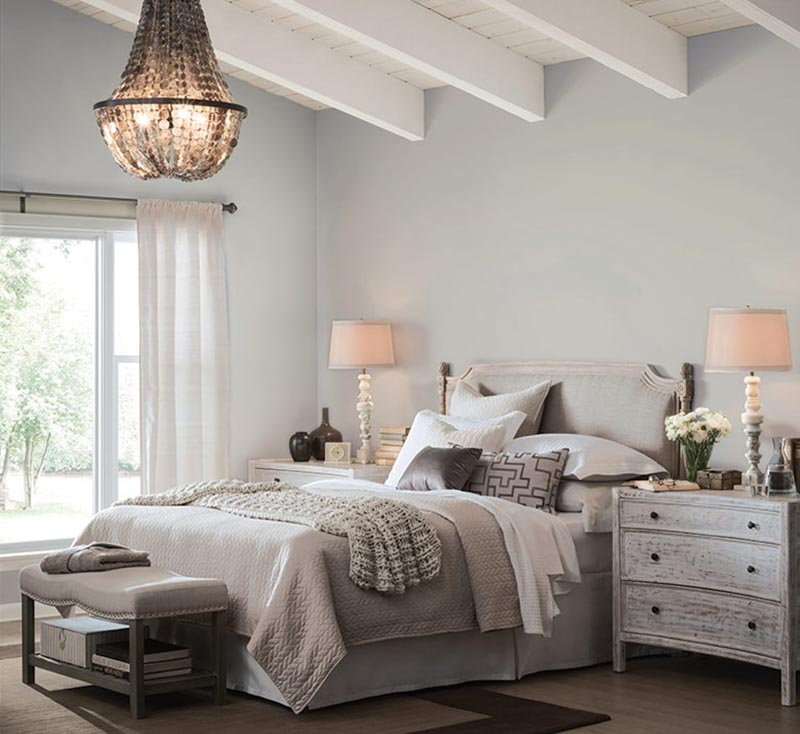 A bedroom with a large bed in a room with walls painted Light French Gray