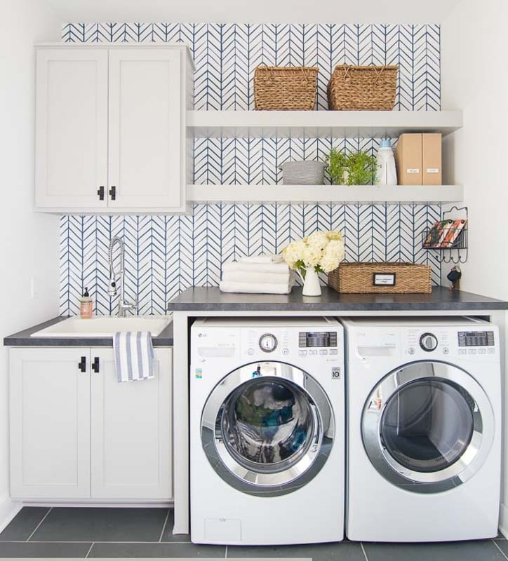 Laundry room with herringbone wallpaper and Sherwin Williams Light French Gray cabinets
