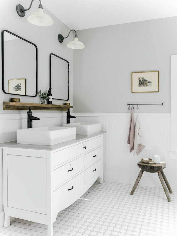 Light French Gray walls in bathroom with double white vanity, schoolhouse lighting and black framed mirrors