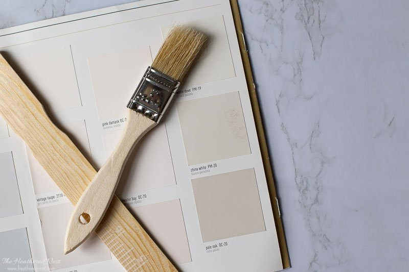 Pale Oak paint swatch on marble background with wooden paint stirrer and paintbrush