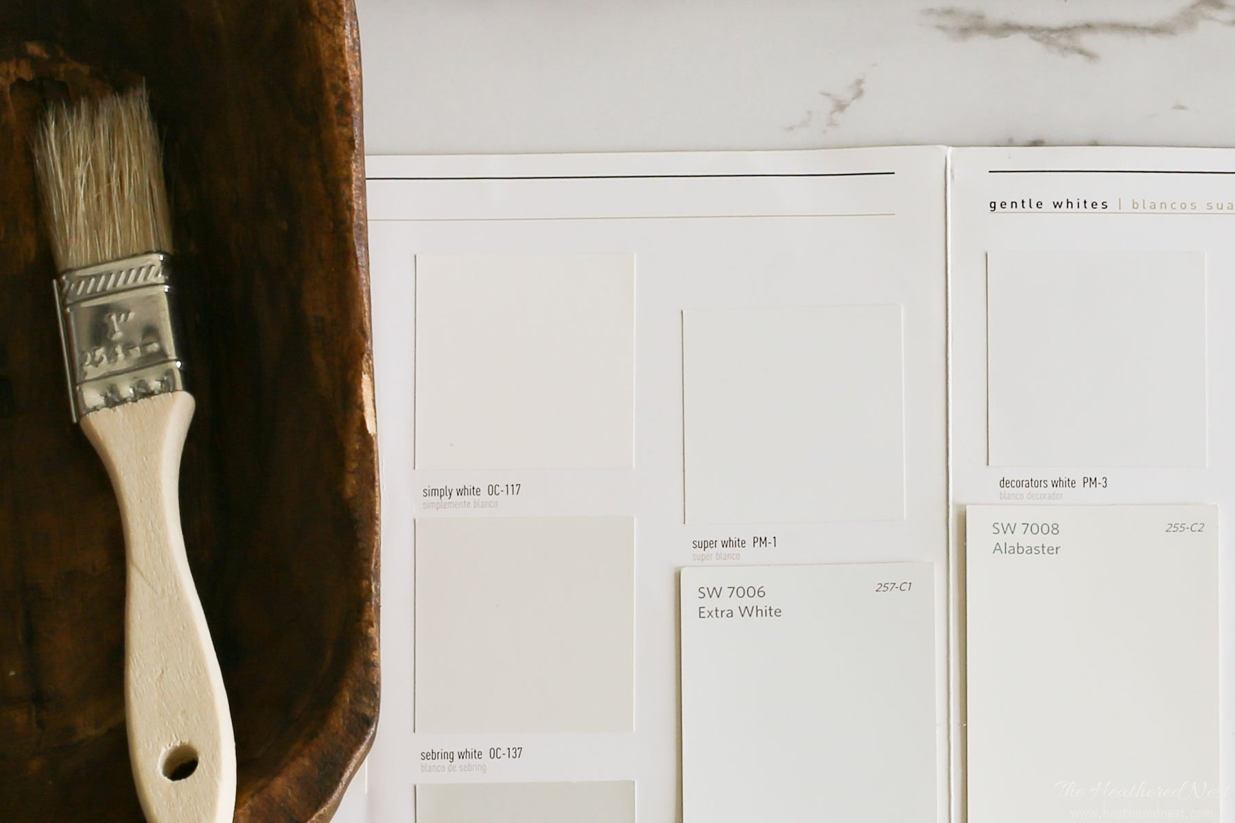 close-up of several sherwin williams whites on a marble table next to a primitive wood bowl with paintbrush - simply white, extra white, alabaster, super white