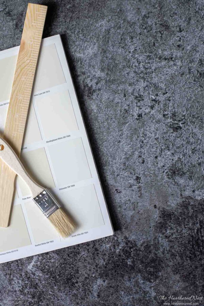 Sherwin Williams Alabaster paint chip on a dark gray background.