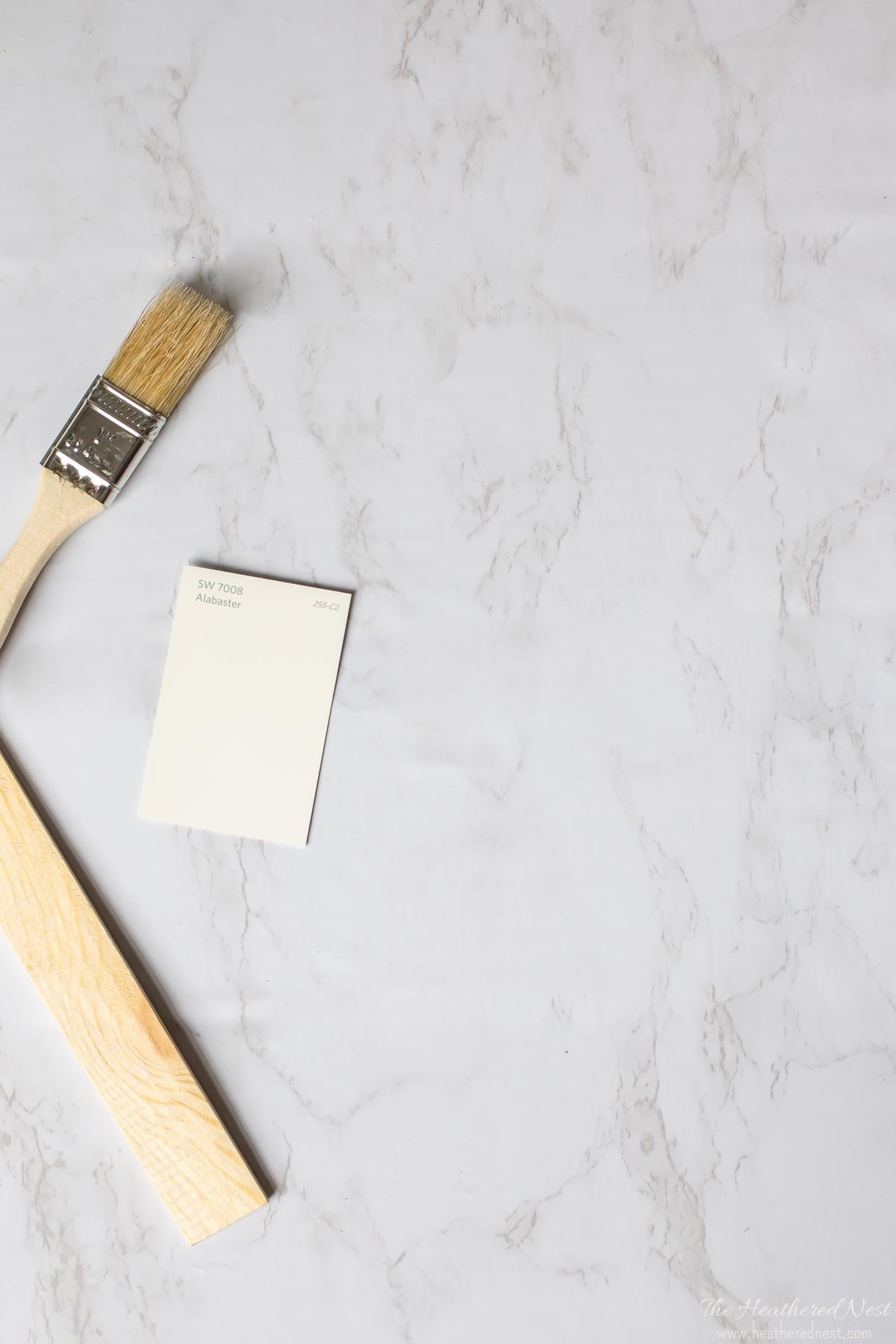 Alabaster paint chip on marble background with paintbrush and wood paint stirrer