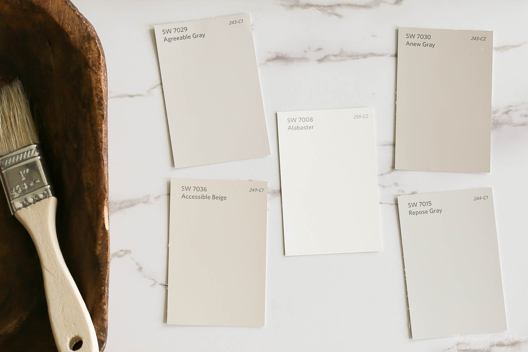 five sherwin williams paint swatches on a marble background next to primitive wood bowl with wood paintbrush. swatches include alabaster, accessible beige, repose gray and