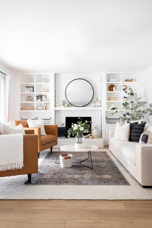 clean, bright white living room with white couch and brown chairs