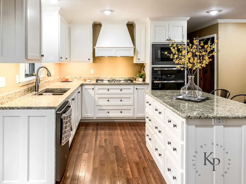 A traditional kitchen with stainless steel appliances and wooden cabinets painted Dover White